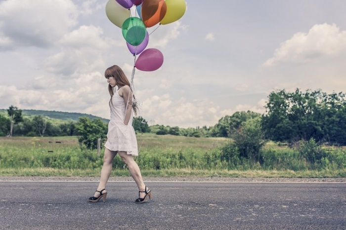 woman-walking-on-road-with-balloons