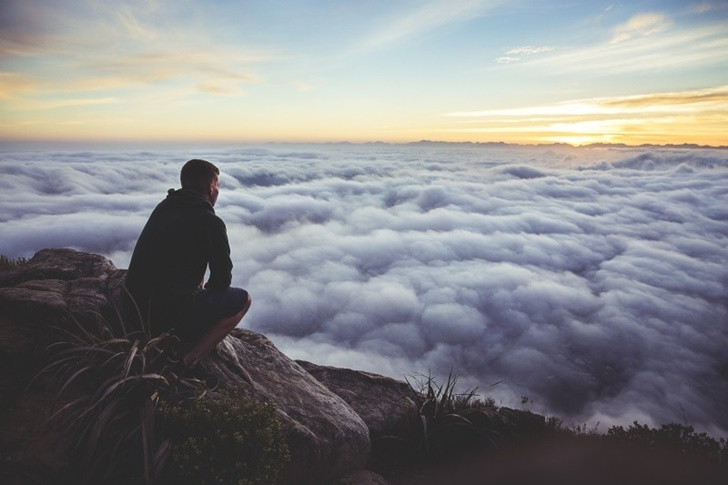 man-sitting-on-rock-looking-at-view-in-clouds-at-sunset (1)